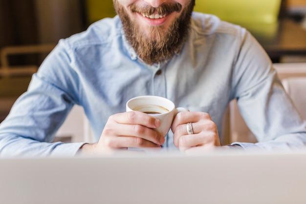 Primo piano di un uomo barbuto felice che beve caffè