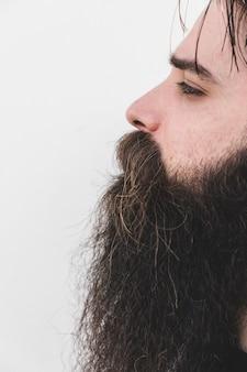 Primo piano di un uomo barbuto isolato sulla superficie bianca