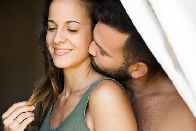 Primo piano di un uomo che bacia il collo della donna