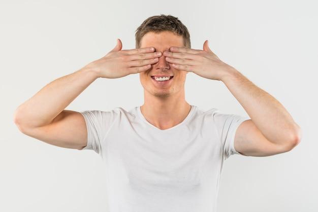 Primo piano di un uomo che la copre occhi di due mani isolate su fondo bianco