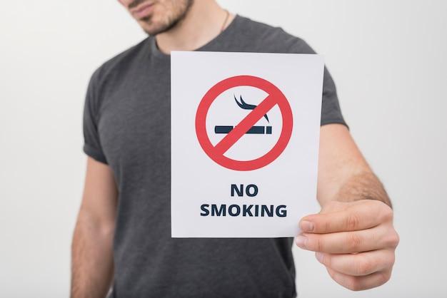 Primo piano di un uomo che mostra il segno non fumatori contro fondo bianco