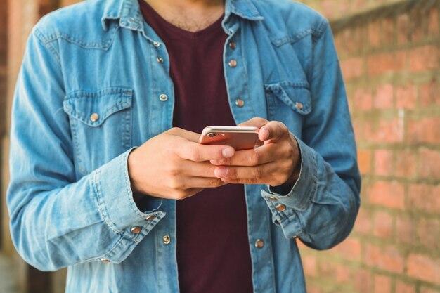 Primo piano di un uomo che per mezzo del suo telefono cellulare.