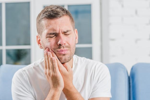 Primo piano di un uomo che soffre di mal di denti