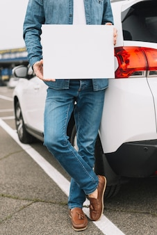 Primo piano di un uomo che sta vicino all'automobile sulla strada che mostra cartello bianco in bianco