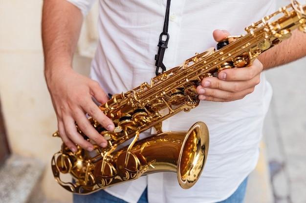 Primo piano di un uomo che tiene il suo sassofono sulla strada