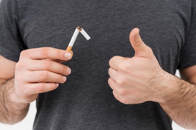 Primo piano di un uomo che tiene la sigaretta rotta che mostra pollice sul segno