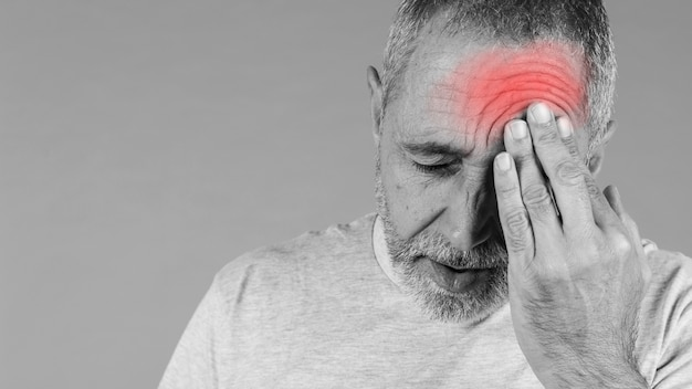 Primo piano di un uomo che tiene la testa nel dolore