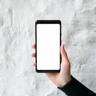 Primo piano di un uomo che tiene uno schermo vuoto smart phone contro il muro di cemento bianco