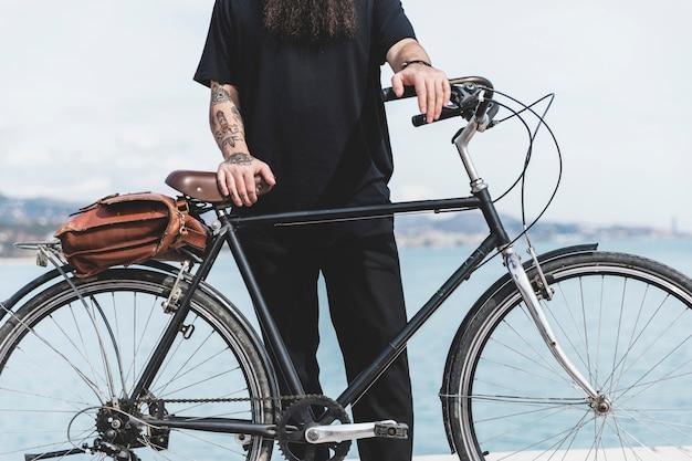 Primo piano di un uomo con il tatuaggio sulla sua mano in piedi con la bicicletta