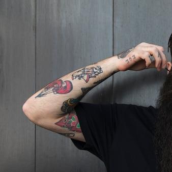 Primo piano di un uomo con il tatuaggio sulla sua mano in piedi contro la parete di legno grigia