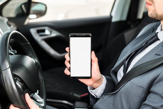 Primo piano di un uomo d'affari che guida l'automobile che mostra telefono cellulare con lo schermo di visualizzazione bianco