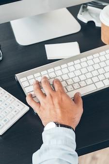 Primo piano di un uomo d'affari che lavora al suo tavolo di lavoro in un ufficio