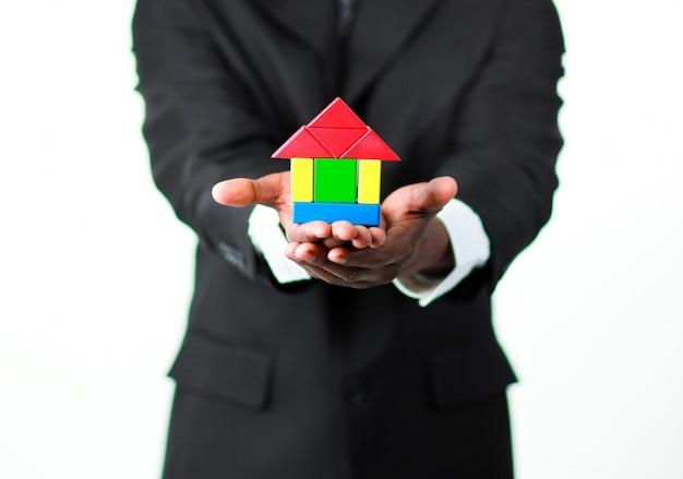 Primo piano di un uomo d'affari che presenta un campione di una casa