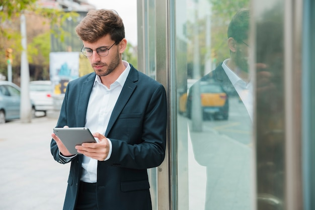 Primo piano di un uomo d'affari che si appoggia vicino alla porta di vetro utilizzando la tavoletta digitale