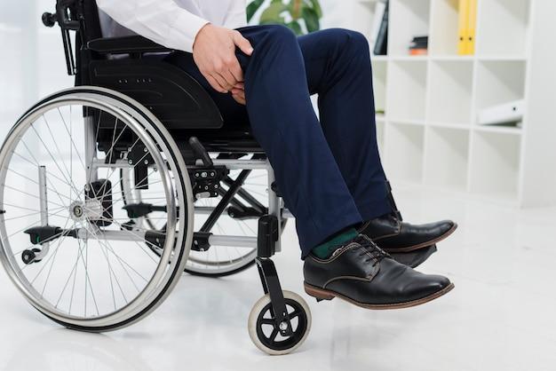 Primo piano di un uomo d'affari che si siede sulla sedia a rotelle che soffre dal dolore della gamba