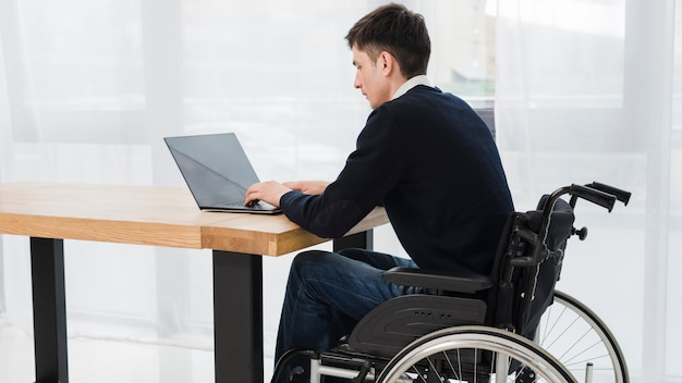Primo piano di un uomo d'affari che si siede sulla sedia a rotelle con laptop in ufficio