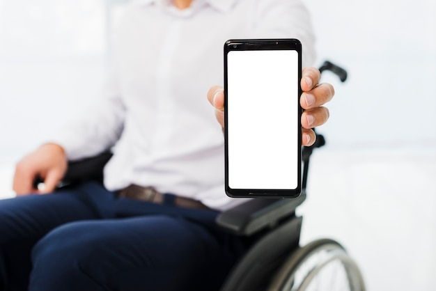 Primo piano di un uomo d'affari che si siede sulla sedia a rotelle, mostrando il telefono cellulare con display bianco