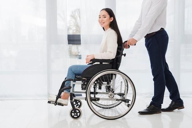 Primo piano di un uomo d'affari che spinge la donna disabile che si siede sulla sedia a rotelle