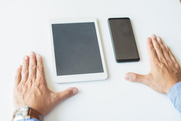 Primo piano di un uomo d'affari con smartphone e tablet computer