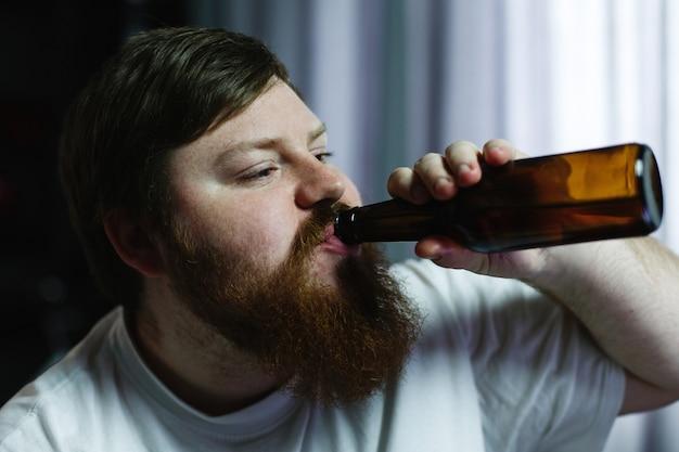 Primo piano di un uomo grasso che sembra brutto mentre beve birra