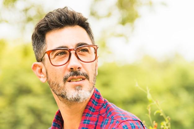 Primo piano di un uomo in occhiali rossi guardando lontano