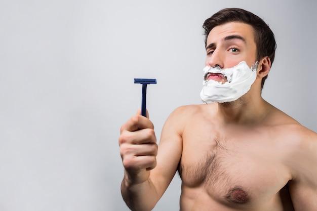 Primo piano di un uomo in topless in piedi nella stanza bianca e che punta sul suo rasoio. pensa che questo sia il miglior rasoio che abbia mai avuto. isolato sul muro bianco.
