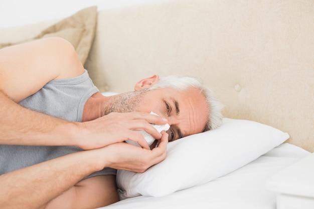Primo piano di un uomo maturo che soffre di raffreddore a letto
