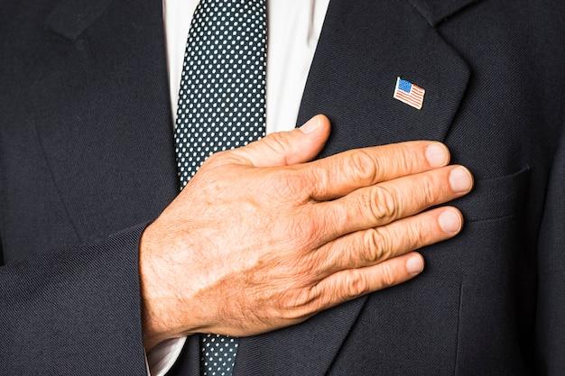 Primo piano di un uomo patriottico con il distintivo degli sua sul suo cappotto nero che tocca la mano sul suo petto