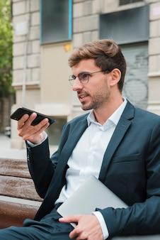 Primo piano di un uomo seduto sulla panchina a parlare al telefono con l'assistente vocale digitale