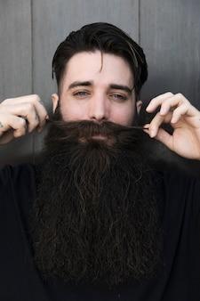 Primo piano di un uomo sorridente che tira i suoi baffi