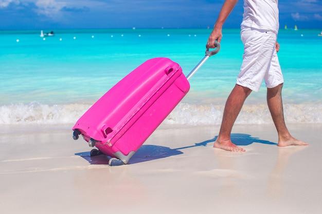 Primo piano di un uomo tira i bagagli sulla sabbia bianca