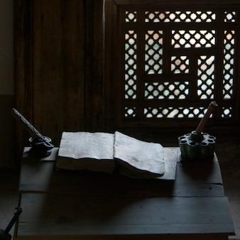 Primo piano di un vecchio libro con inchiostro bene sul tavolo a ben youssef madrasa, medina, marrakesh, marocco