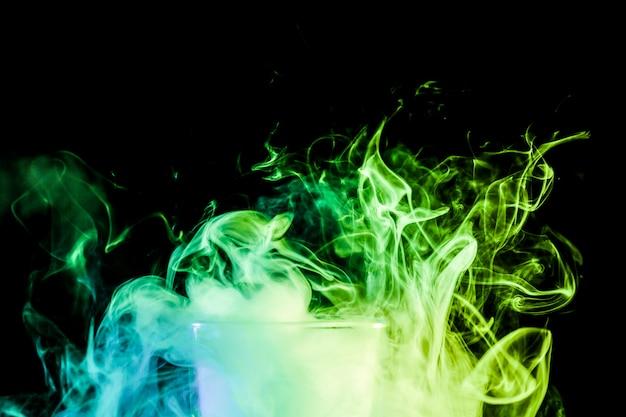 Primo piano di un vetro trasparente riempito con una nuvola da un verde vape fuma e si leva in piedi su uno sfondo nero isolato