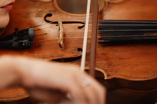 Primo piano di un violino con un inchino. orchestra marrone violino. dita sulla tastiera del violino.
