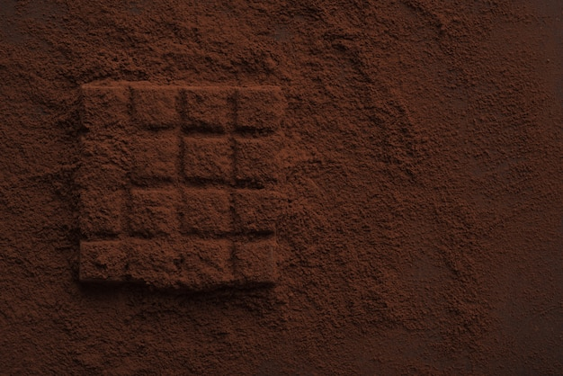 Primo piano di una barretta di cioccolato fondente ricoperta di cioccolato in polvere