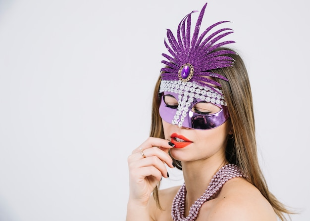 Primo piano di una bella donna che indossa la maschera di carnevale e collana di perle