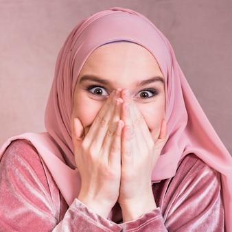 Primo piano di una bella donna eccitata con le sue mani sulla bocca