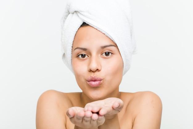 Primo piano di una bella e naturale giovane donna ispanica con un asciugamano sulla testa