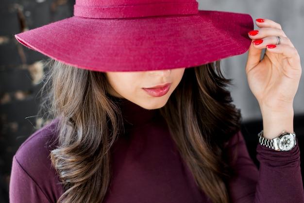 Primo piano di una bella giovane donna con cappello rosa