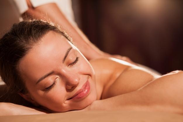 Primo piano di una bellissima giovane donna felice sorridente con gli occhi chiusi, godendo il massaggio rilassante al centro benessere. bella femmina che si distende al salone di coccole, copia spazio. servizio, viaggi, turismo
