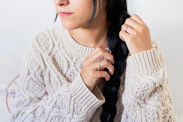 Primo piano di una bellissima giovane donna sorridente e facendo una treccia tra i capelli in abito invernale a casa