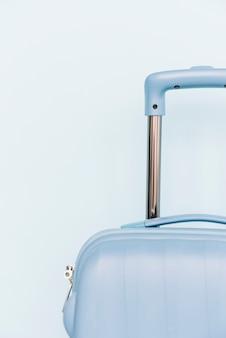 Primo piano di una borsa dei bagagli di plastica di viaggio su fondo blu