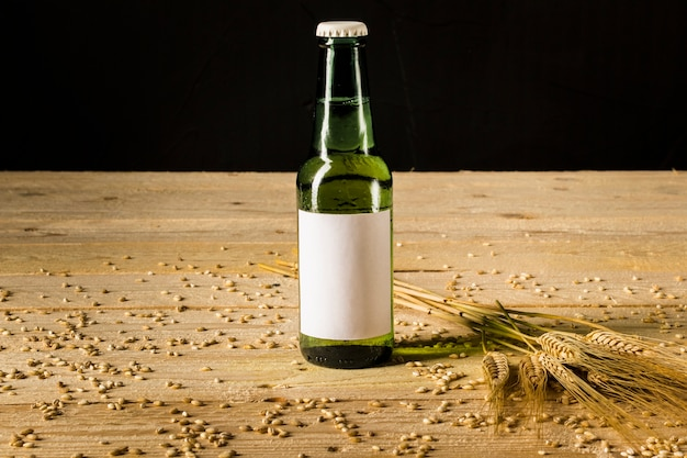 Primo piano di una bottiglia alcolica e spighe di grano sulla plancia di legno