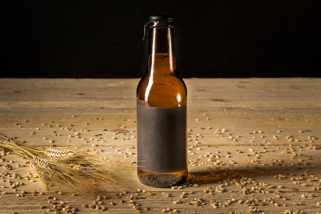 Primo piano di una bottiglia da birra e spighe di grano su venatura del legno