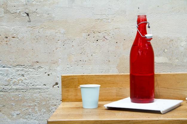Primo piano di una bottiglia di acqua rossa e vetro su un tavolo del ristorante contro un muro di pietra leggera