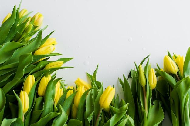 Primo piano di una bracciata di tulipani gialli con gocce d'acqua.