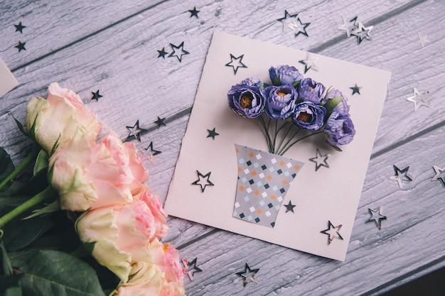 Primo piano di una cartolina fatta in casa con fiori blu in una pentola.