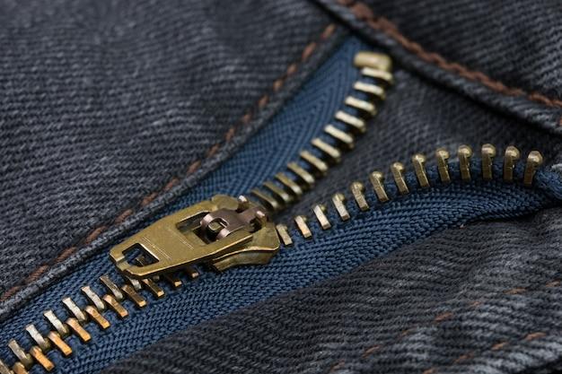 Primo piano di una cerniera color rame con jeans neri