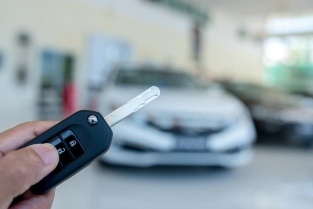 Primo piano di una chiave dell'automobile - un giovane che tiene una nuova chiave dell'automobile nello showroom dell'automobile, nuova chiave