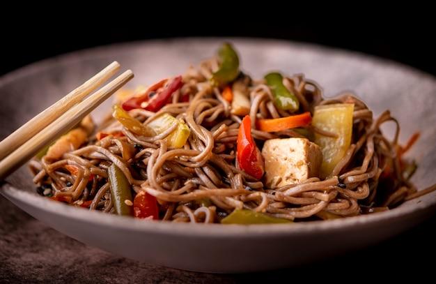 Primo piano di una ciotola di verdure e noodles